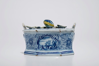 A Dutch Delft blue and white butter tub with polychrome finial, 18th C.