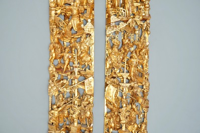 A pair of Chinese carved, lacquered and gilt wood panels with figurative designs, 19th C.