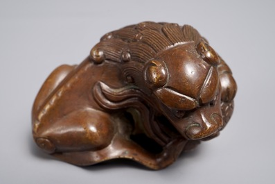 A Chinese bronze scroll or paper weight shaped as a Buddhist lion or Shishi with a ball, 17/18th C.