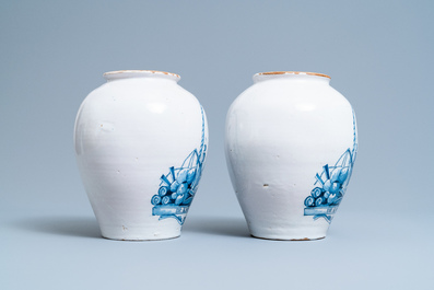 A pair of Dutch Delft blue and white tobacco jars with a trader, 18th C.