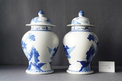A pair of Chinese blue and white vases and covers with figures in a landscape, 19th C.