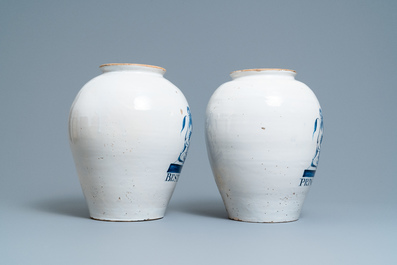 A pair of large Dutch Delft blue and white tobacco jars with the arms of Amsterdam, 18th C.