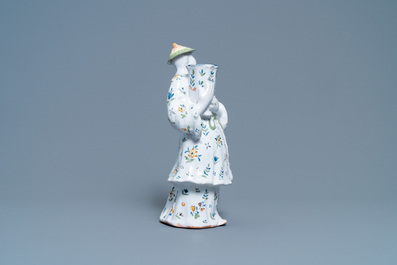 A polychrome French faience candle holder in the shape of a Chinaman, Lille, 18th C.