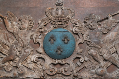 A large polychromed carved oak panel with putti and trophies flanking the royal coat of arms of France, 18th C.