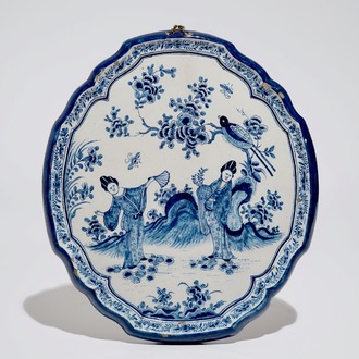 A Dutch Delft blue and white chinoiserie plaque with two ladies, 18th C.