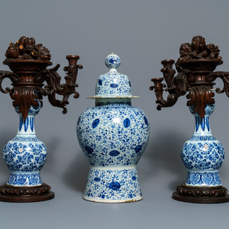 A Dutch Delft blue and white three-piece garniture with carved wooden candleholders, 18th C.