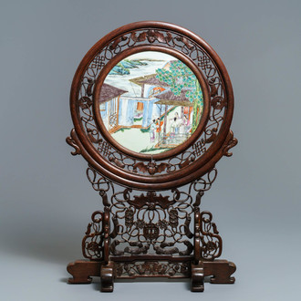 A Chinese carved wooden screen with a famille rose plaque, 19/20th C.