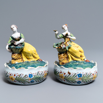 A pair of polychrome Dutch Delft butter tubs with ladies selling flowers and fruits, 18th C.