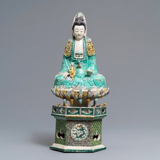 A Chinese verte biscuit group of Guanyin with child on a lotus throne, Kangxi