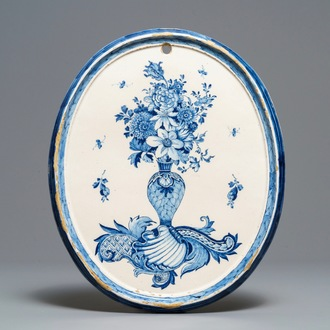 A fine oval Dutch Delft blue and white plaque with a flower vase, 18th C.