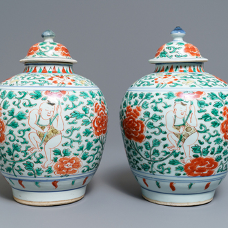 A pair of Chinese wucai vases and covers with boys among peonies, Transitional period