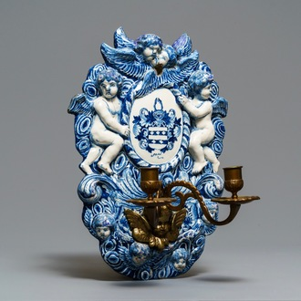 A large Dutch Delft blue and white armorial relief-decorated plaque, early 18th C.