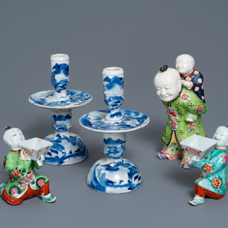 A pair of Chinese blue and white candlesticks and three famille rose figures of boys, 19th C.