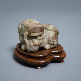 A Chinese pale grey-brown jade model of a Buddhist lion, 19/20th C.
