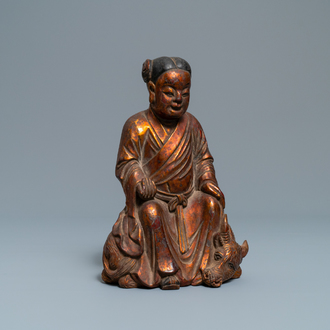 A Chinese gilt and laquered wooden group with a boy on an ox, 18/19th C.