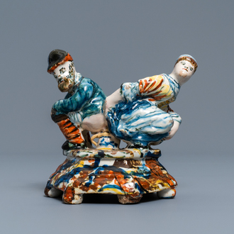 A polychrome Dutch Delft group of a man and a woman on a chamberpot, 18th C.