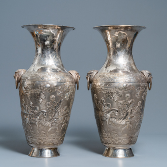 A pair of exceptional large Chinese relief-decorated silver vases, 19th C.