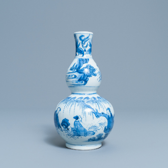 A Chinese blue and white double gourd vase with figures in a landscape, Transitional period