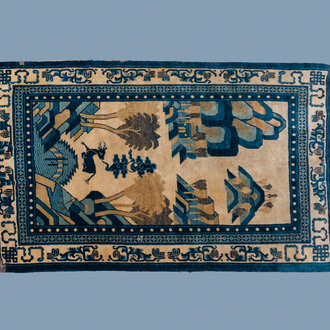 A rectangular Chinese Beijing silk carpet with a deer in a landscape, 19th C.