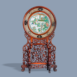 A massive Chinese carved wooden screen with a round famille verte plaque and polychrome lacquer, 19th C.