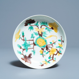 A Chinese sancai-glazed plate with carved floral design, Kangxi