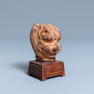 A Chinese painted pottery model of a mythical beast's head, Tang