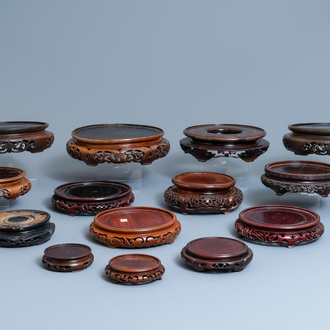 Fourteen Chinese reticulated round carved wooden stands, 19/20th C.