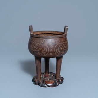 A Chinese inlaid bronze tripod censer on wooden stand, Ming
