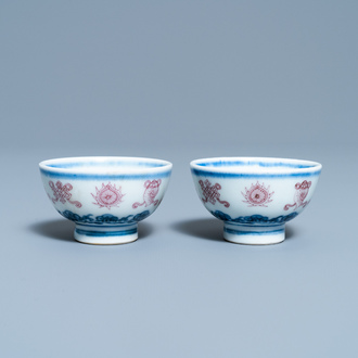 A pair of Chinese blue, white and copper red 'bajixiang' tea bowls, 4-character mark, 19/20th C.
