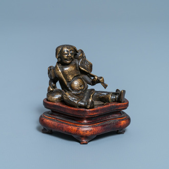 A Chinese bronze 'Liu Hai' scroll weight on wooden stand, Ming