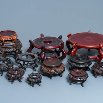 Twelve large round Chinese carved wooden stands, 19/20th C.