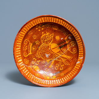 A Dutch slip-decorated pottery dish with an owl, dated 1585