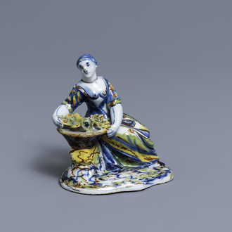 A polychrome Dutch Delft figure of a lady selling flowers, 18th C.