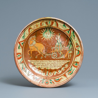 A German slip-decorated inscribed pottery dish with a ploughing farmer, Lower Rhine region, 2nd half 18th C.