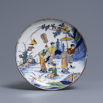 A polychrome Dutch Delft chinoiserie plate with figures in a garden, 18th C.