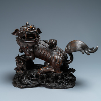 A Chinese bronze model of a Buddhist lion on a finely carved wooden stand, 18th C.