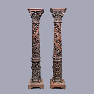 A pair of reticulated carved oak Corinthian columns with cherub heads and vines, 17th C.