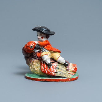 A polychrome Dutch Delft box and cover in the shape of a boy on a bird, 18th C.