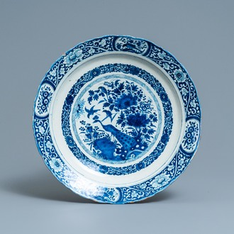 A Dutch Delft blue and white dish with a peacock in a Chinese garden, dated 1693