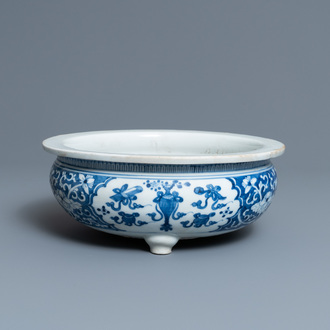 A Chinese blue and white tripod censer with antiquities, Kangxi