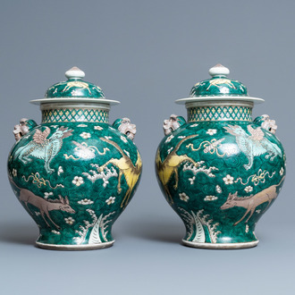 A pair of Chinese famille verte 'mythical animals' vases and covers, 19th C.