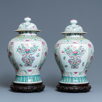A pair of Chinese famille rose vases and covers, 19th C.