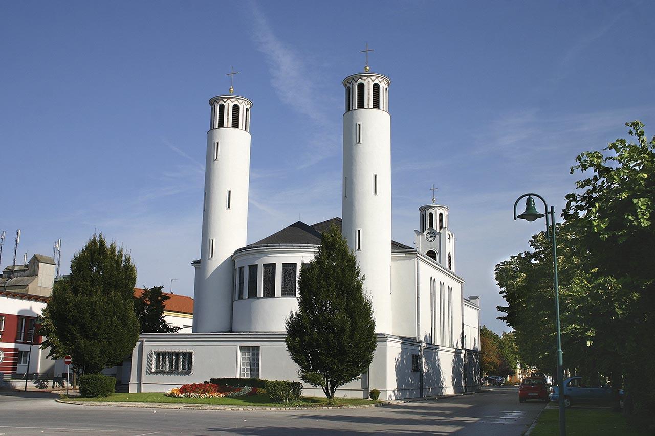 Die wegen ihrer ungewöhnlichen Architektur bekannte Pfarrkirche ist neben der Brücke von Andau das Wahrzeichen der Marktgemeinde.