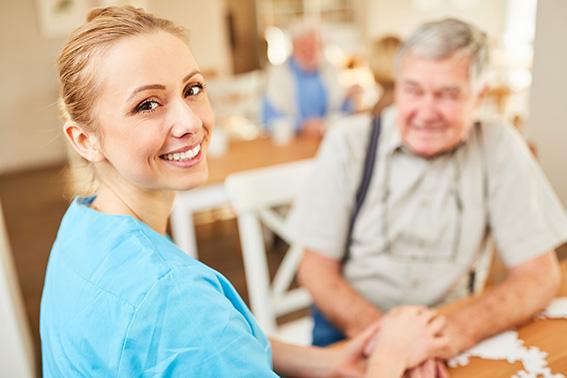 Lächelnde Pflegehilfe tröstet einen Senior.
