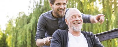 Junger schiebt alten im Rollstuhl