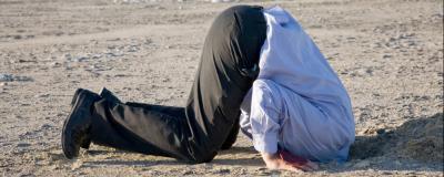 Mann steckt Kopf in den Sand