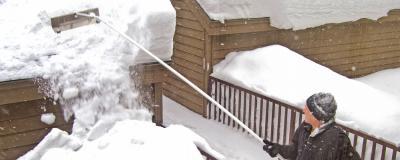 Mann räumt Schnee von einem Haus