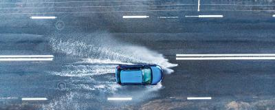 Blaues Auto auf nasser Straße