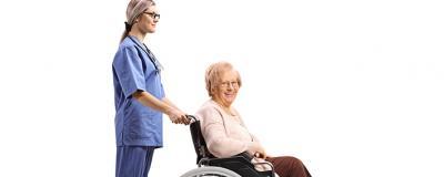 Pflegerin schiebt Frau in Rollstuhl