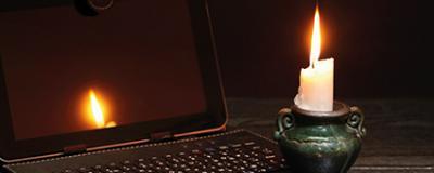Laptop und Kerze während eines Blackouts